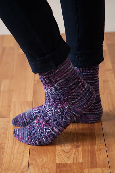 Model's feet on hardwood floor wearing meandering socks.