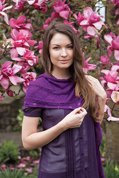 Model wearing the Kinross Avenue Wrap in front of a tree covered in pink flowers.