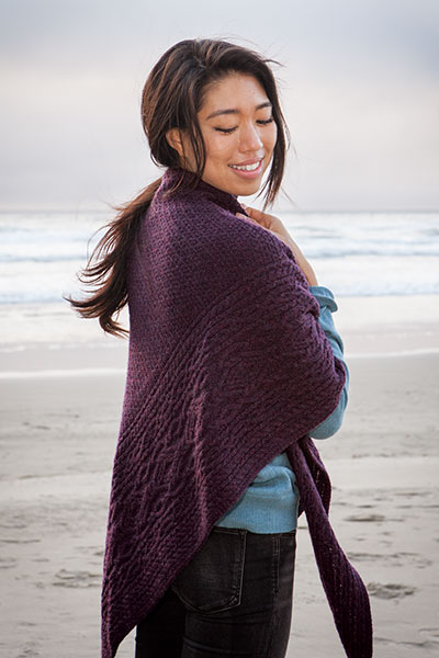 A model on the beach wearing the violet Arisaig shawl.