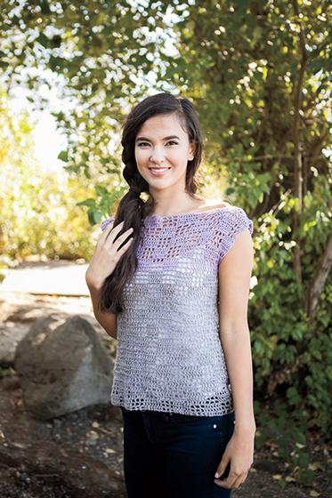 Serin Crochet Tee, designed by Tian Connaughton. A woman is shown standing in a wooded area wearing a delicate lavender sweater.