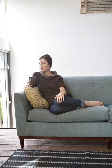 Woman wearing the Jayashri Pullover while reclining on couch.