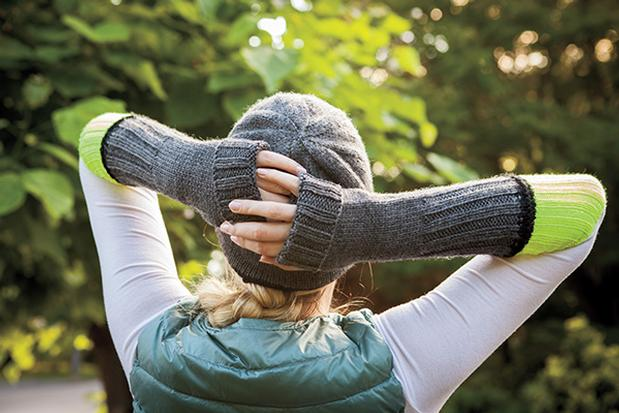 A woman is shown with her back to the camera, standing in a wooded area, modeling a gray knitted hat and knitted arm warmers in gray and neon yellow. The Brightwood Hat & Mitts pattern, a design by Tian Connaughton for Knit Picks.