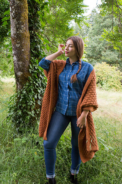 Model wearing the Weft Wrap in a forested area.