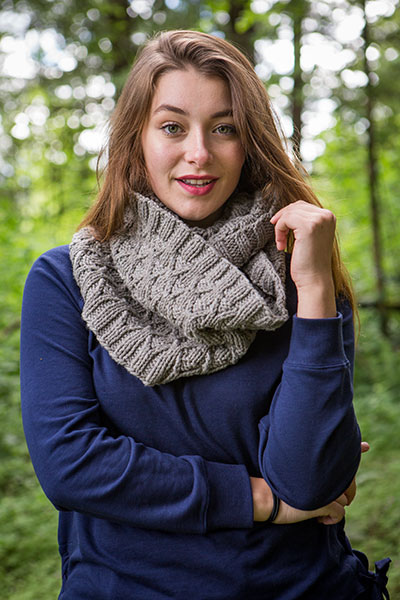 Model wearing the Wynt Cowl in a forested area.