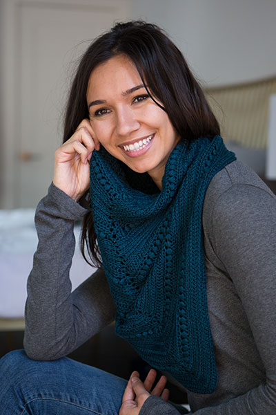 A woman is sitting on a couch modeling a deep blue crocheted neck scarf. It's the Simple Cowl Neck Shawl, a pattern by Tian Connaughton for Knit Picks.