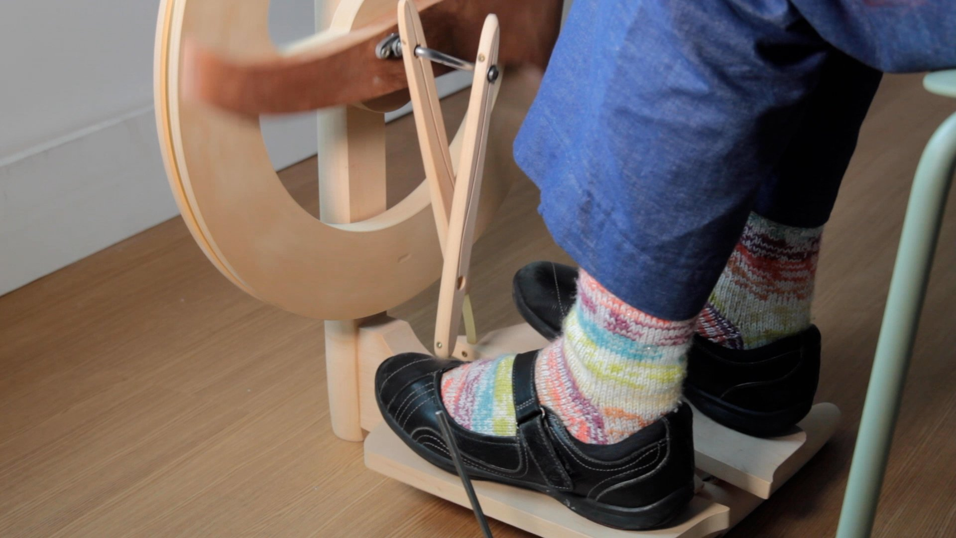 Someone using their foot to spin a spinning wheel