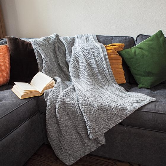 A gray knitted blanket draped on a couch. The Abrigado blanket pattern: Made in bulky yarn with an arrow pattern pleasing to the eye, you'll want one for every room in your home.
