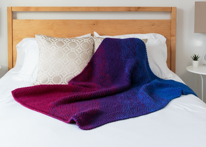 Continuation Blanket: A knitted blanket with a diagonal gradient going from maroon to purple to blue.