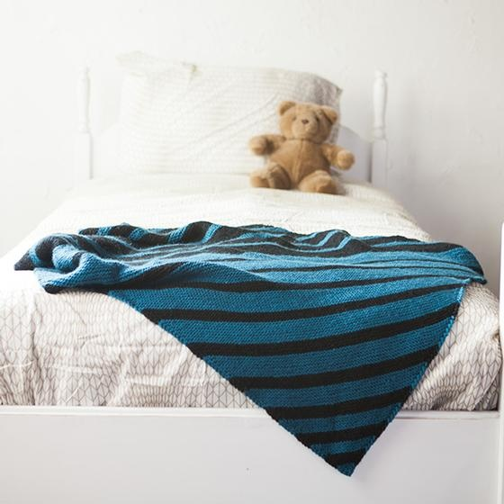 A blue knitted blanket with diagonal stripes of blue and black.