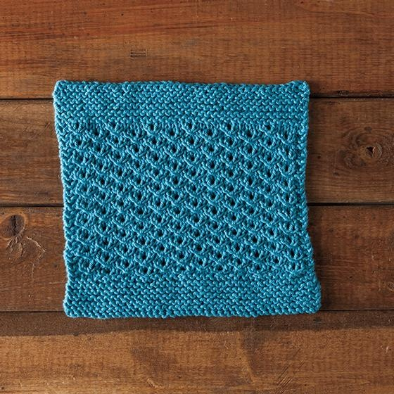 Sunny Days Dishcloth: A blue knitted dishcloth with a garter stitch border and a lace-like middle