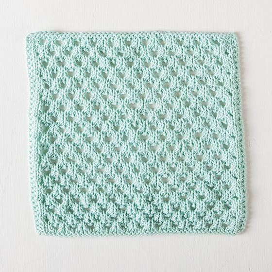 Honeycomb Dishcloth: A mint colored knitted dishcloth with a diagonal woven pattern