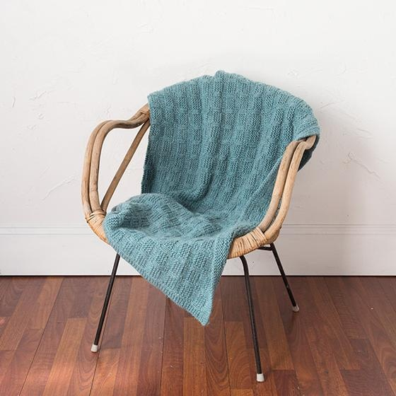 A green knitted blanket with a basketweave pattern is draped on a wicker chair