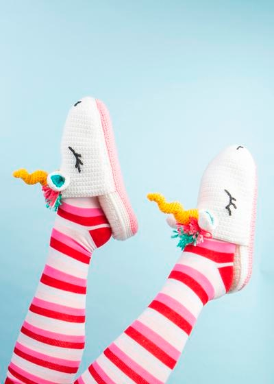 Two feet model a pair of crochet slippers that look like unicorns.