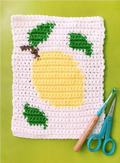 An image of a crochet block with a lemon design on it. A crochet hook and scissors.