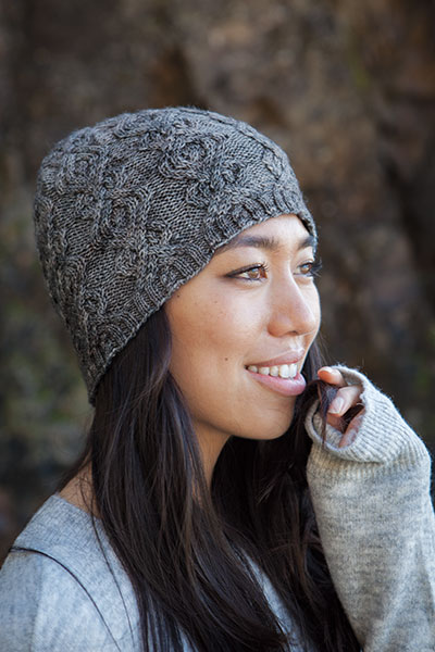 A woman wearing an intricately cabled knit hat.